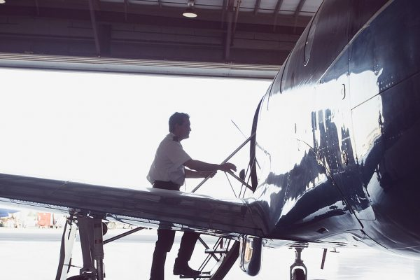 Caucasian pilot boarding airplane in hangar